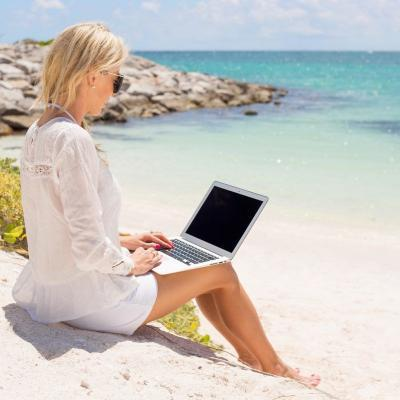 Businesswoman working with laptop computer on the beach.