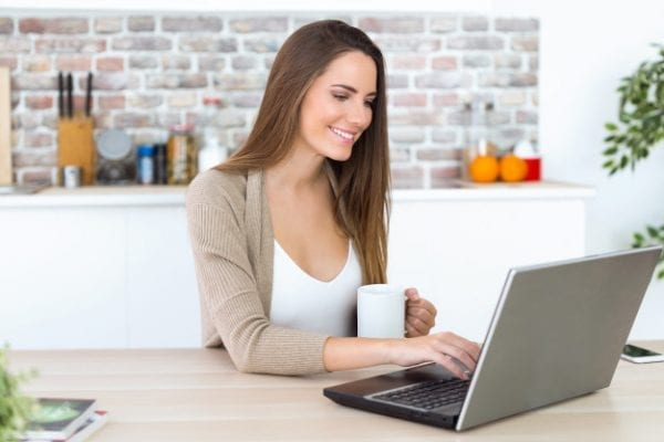 beautiful-young-woman-using-her-laptop-kitchen_1301-7666